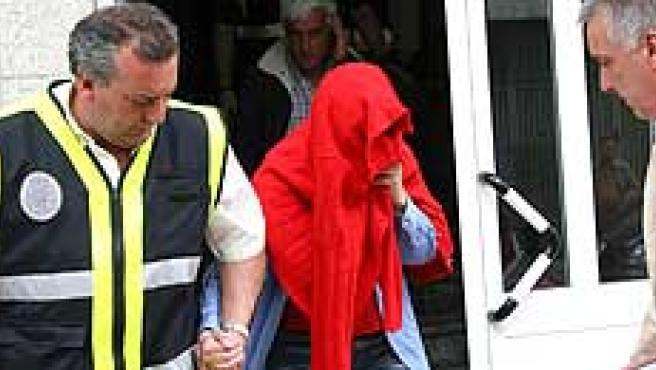 Un policía acompaña a una de las mujeres detenidas ayer (Foto: Efe)
