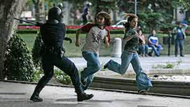 Un policía, instantes antes de propinar un porrazo a un joven en el Paseo del Prado (Jorge París).