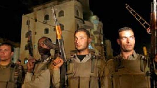 Militantes palestinos montan guardia en la sede del oficina del primer ministro en Ramala, Cisjordania. (Efe)