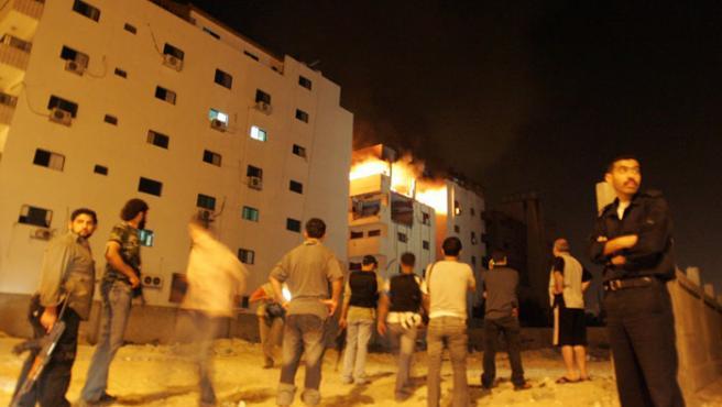 Hombres alrededor del ministerio palestino en llamas.(Mohammed Salem / REUTERS)
