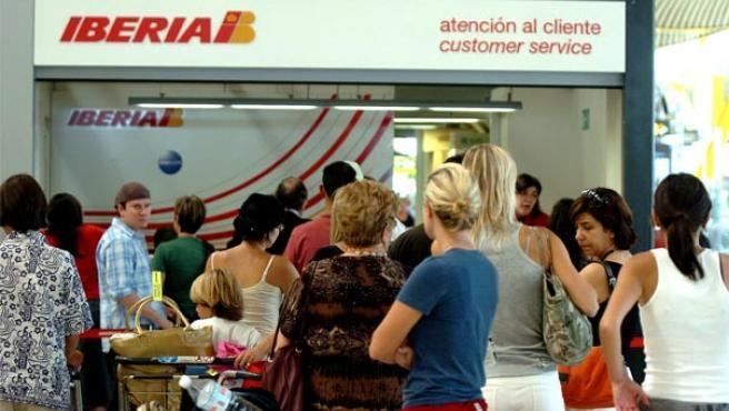 Varios pasajeros hacen cola en el mostrador de 'atención al cliente' de Iberia, en el aeropuerto de Barajas en Madrid (Foto: Efe)