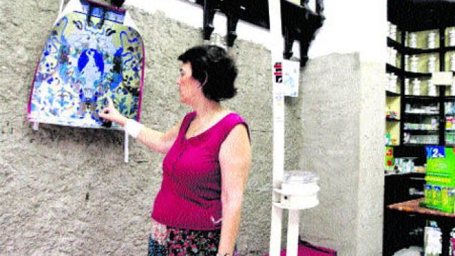 María Luisa Murillo, propietaria de la farmacia, muestra la fotografía que hoy sustituye al mural cerámico(Aníbal González).