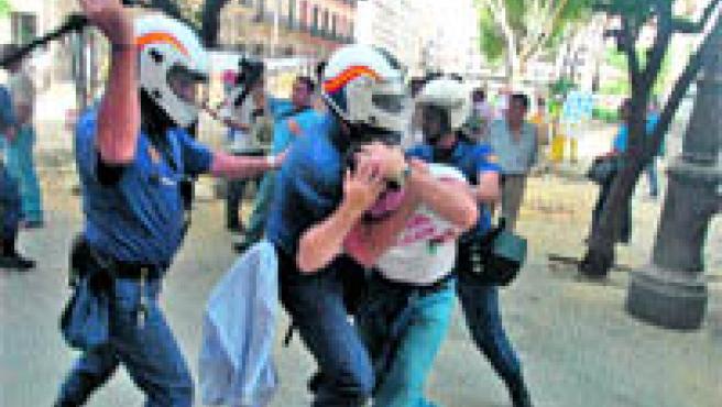 Varios policías golpean con sus porras y tratan de inmovilizar a uno de los trabajadores de astilleros, ayer (K. R.).