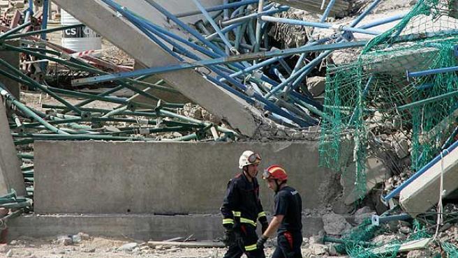 Bomberos entre los escombros del edificio desplomado.(J.J. Guillén/Efe)