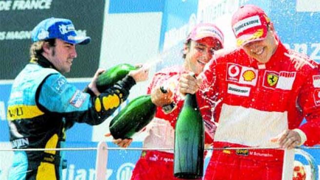 Fernando Alonso rocía con champán a los pilotos de Ferrari Michael Schumacher y Felipe Massa. (EFE)