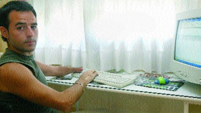 Alejandro Pérez muestra cómo puede trabajar en una oficina sin la mano izquierda.Fran Manzanera.