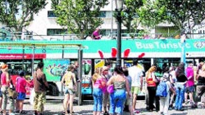 Cues de turistes a la parada de Plaça Catalunya per agafar el bus.