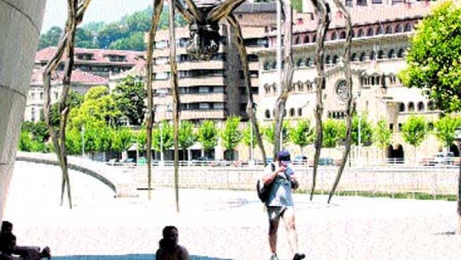 Varios turistas se esconden del sol, a mediodía de ayer, junto al Museo Guggenheim.(Begoña Hernández)