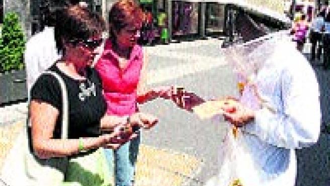 Apicultores regalaron ayer 1.000 tarros de miel en la calle Santiago para criticar la situación del sector.(P. ELÍAS)