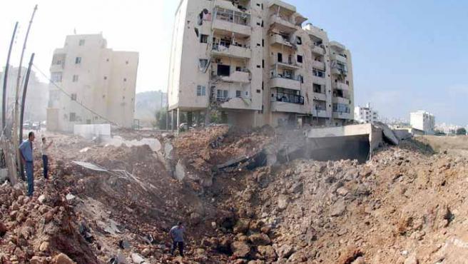 Civiles libaneses miran un cráter causado por una bomba israelí en Chowifat, cerca de Beirut (Wael Hamzeh / EFE)