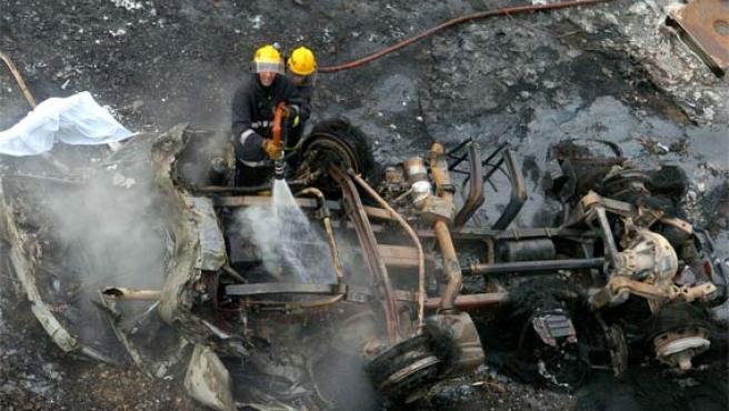 Unos bomberos extinguen el incendio provocado por la explosión del camión (Foto: Efe)