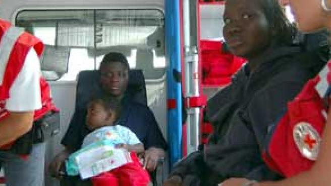 Dos mujeres y uno de los bebés que llegaron en patera son atendidos por miembros de la Cruz Roja