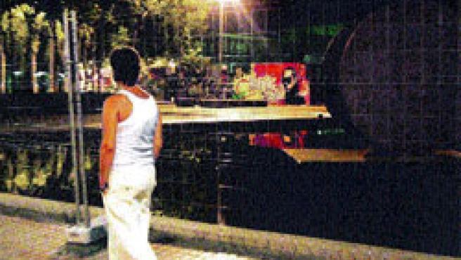 Un joven pasa delante de las vallas colocadas de noche en el Parc de les Tres Xemeneies. (Hugo Fernández)