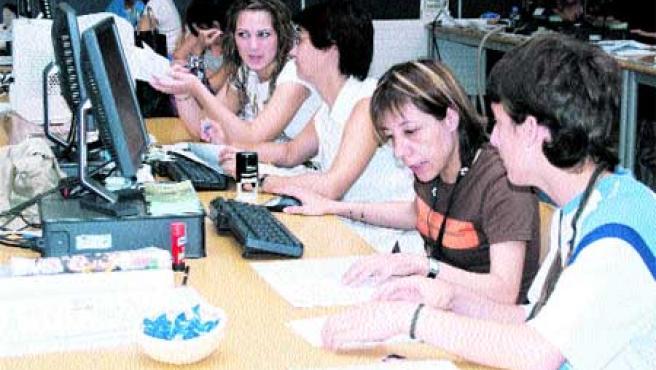 Alumnos acompañados de sus familiares, ayer, en el aula de ordenadores, en La Casilla, donde se realizan las matrículas.(Begoña Hernández)
