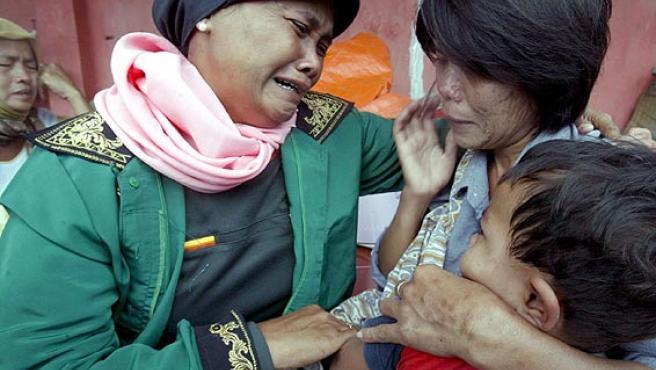 Una mujer se reencuentra con su vecina en un campo de refugiados después del terremoto que provocó un tsunami en Java (Bagus Indahono / EFE)