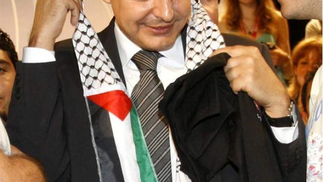 """Zapatero se pone el pañuelo(denominado """"kufiya"""") que le brindan en un acto del Foro Joven Internacional en Alicante.(Morell / Efe)"""