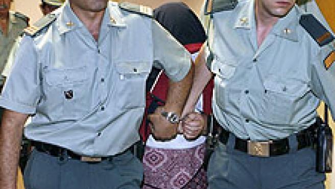 Dos agentes acompañan a la presunta asesina a declarar ante el juez. (Andreu Dalmau/Efe)