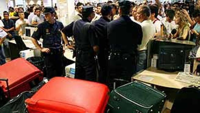 Pasajeros protestando frente a los mostradores de Iberia, bajo la vigilancia de la Policía y rodeados de cientos de maletas.(A.Gea / Reuters)