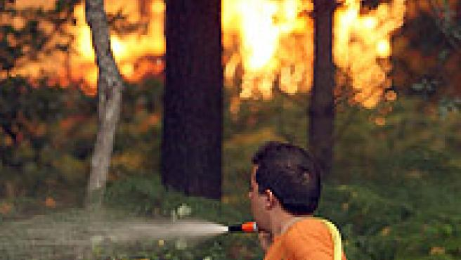 Un hombre trabaja en las labores de extinción del incendio que afecta a la localidad pontevedresa de Arcade. (EFE)