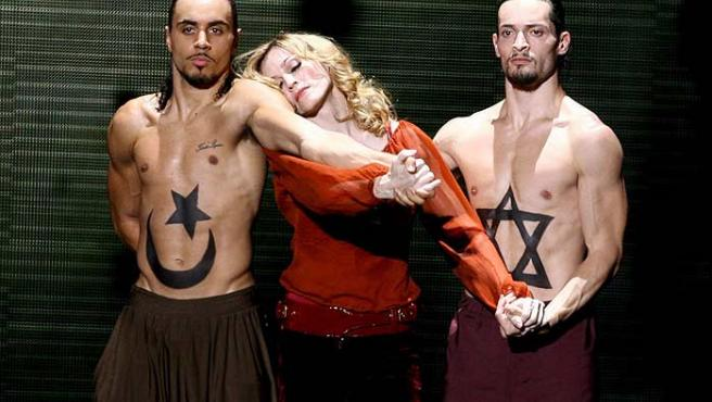 Madonna, durante su concierto en Roma, con dos bailarines que llevan pintados símbolos musulmanes y judíos. (Ettore Ferrari / EFE)