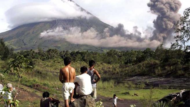Varias personas observan la erupción del volcán Mayón en el poblado de Matanag (Dennis M. Sabangan / EFE)