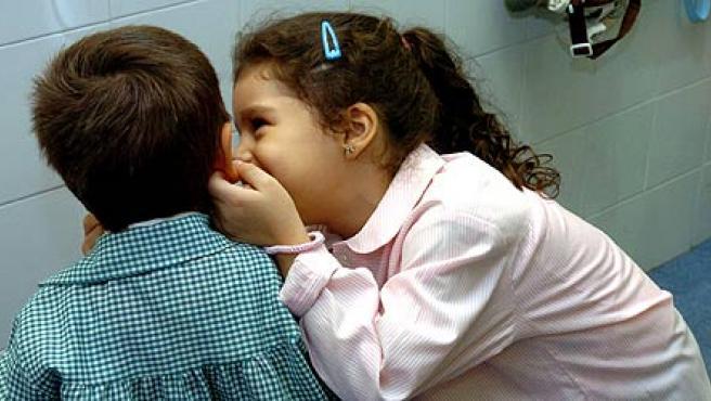 Dos niños cuchichean poco antes de comenzar la clase en el centro escolar José Calvo Sotelo, en Madrid.(EFE/Angel Díaz)