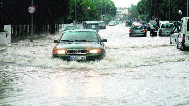 Un cotxe circula amb dificultats per la carretera de Salou a Cambrils inundada per culpa del temporal d'ahir. (Jaume Sellart / Efe)