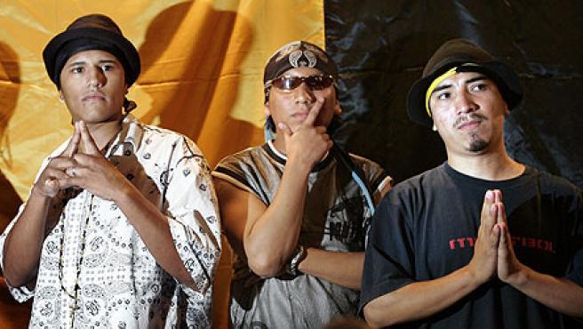 Tres jóvenes de los Latin Kings hacen los gestos habituales de los miembros de la nueva asociación cultural. (Alberto Estévez/Efe)