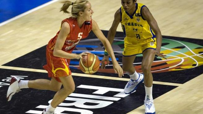 La jugadora de la selección española de baloncesto Marta Fernández lleva el balón marcada por la brasileña Iziane(Efe)