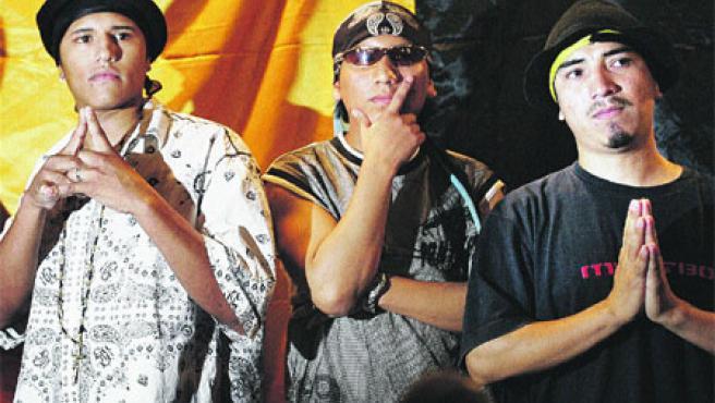 Tres miembros de Reyes y Reinas Latinos, ayer, posando delante de su bandera en el acto de presentación en sociedad. (Alberto Estévez / Efe)