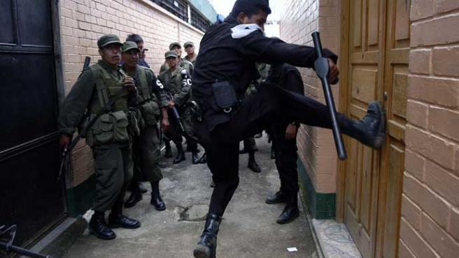 Un agente de la Policía de Guatemala intenta entrar a la Granja Penal de Pavón (Ulises Rodríguez / Efe)