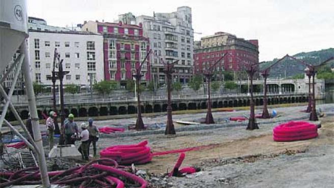 Varios obreros descansan, ayer, tras la colocación de la estructura de los tinglados. (M. Romero)