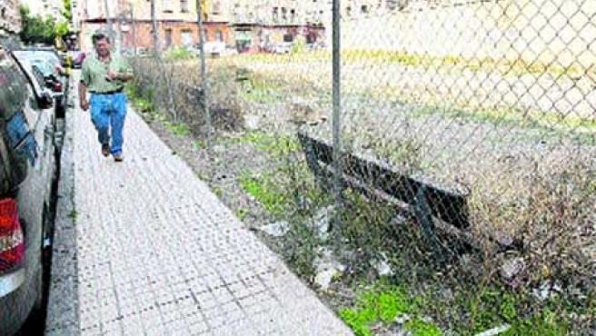 Los bancos del solar de la calle Mariano Turmo están encerrados tras una valla desde hace 15 meses. (F. Simón)