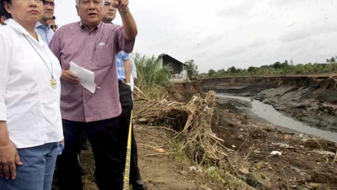 La presidenta filipina, Gloria Macapagal Arroyo (izqda.), y el gobernador provincial, Ayong Maliksi, miran las secuelas del paso del tifón. (EFE)