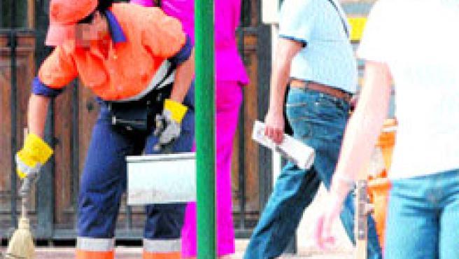 Una trabajadora de Agricultores de la Vega recoge basura en el centro de Valencia remangada. (P. Argente)