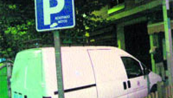 Un vehículo municipal estacionado en una aparcamiento para motos.