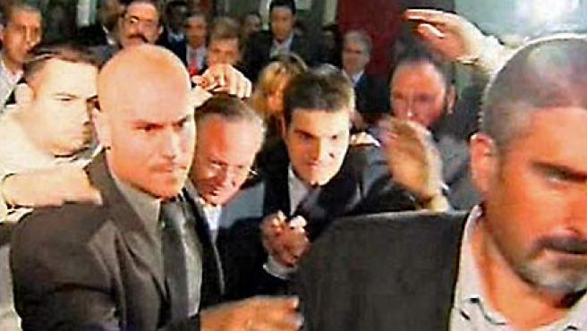 El presidente del PP de Cataluña, Josep Piqué, sale protegido por guardaespaldas del centro cultural donde se celebró el mitin. (EFE)