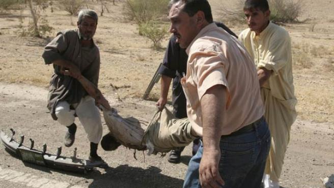 Un grupo de hombres traslada a un iraquí muerto en la ciudad de Tikrit, al norte de Bagdad (Nuhad Hussin / Reuters)