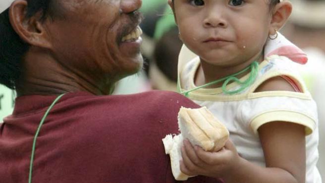 """Una niña filipina se manifiesta junto con su padre con un cartel en el que se lee: """"Comida para todos"""".(Efe)"""