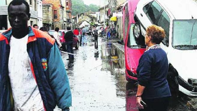 Varios de los turismos arrastrados por la riada, ayer, en el centro de la localidad de Sabarís.(M. Vila)