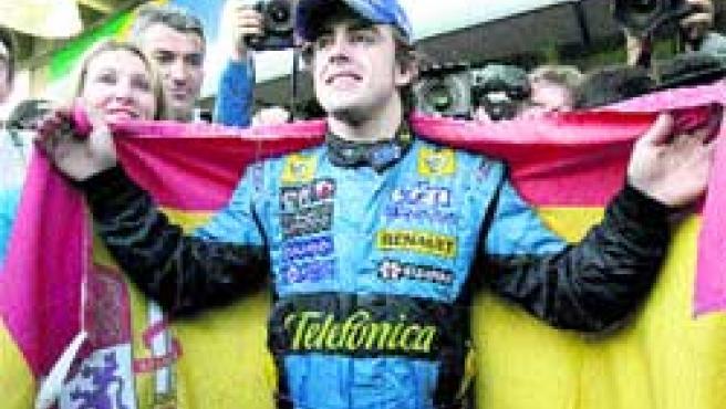 Alonso celebra su título mundial con una bandera de España en el circuito brasileño de Interlagos. (EFE)