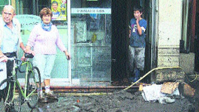 Luisa, la dueña del local, trataba ayer de limpiar parte del lodo que inundó la panadería Sabarís. (M. Vila)