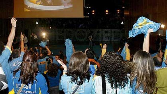 Seguidores de Alonso contemplan al piloto en la pantalla gigante del auditorio de Oviedo. (Efe)