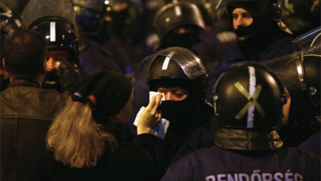 Una joven ayuda a un antidisturbios durante las protestas contra el Gobierno en Budapest (Reuters)