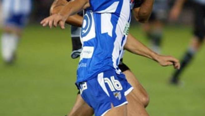 El defensa del Málaga F.C. Armando (d), trata de irse de Gari Uranga. (Efe)