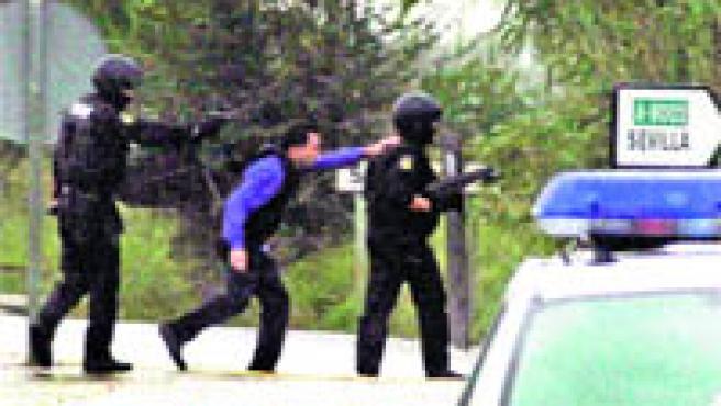 Dos agentes de la Policía Nacional protegen al negociador del presunto secuestro (Aníbal González).