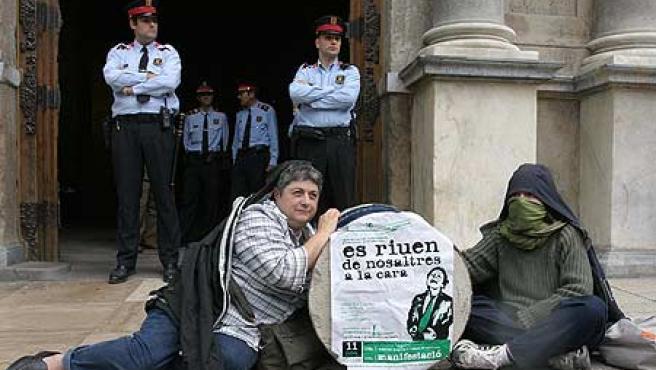 Dos jóvenes se han encadenado a una bloque de cemento frente al Palau de la Generalitat. (Hugo Fernández)