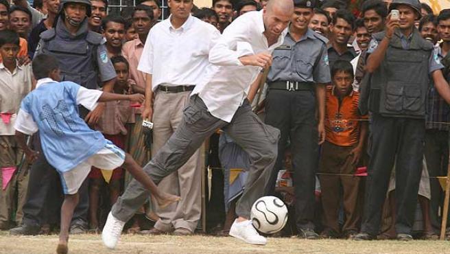 Zidane intenta regatear a un niño ante la mirada de un gran número de personas. (Efe)