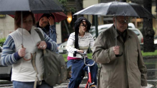 Una joven en bicicleta se protege de la lluvia que cae desde primeras horas de la mañana en Valencia (Foto: Efe)