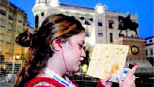 Una joven turista usa la audioguía ayer por la tarde en la Plaza de las Tendillas (Roldán Serrano).